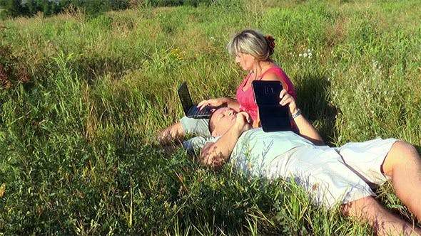 Thumbnail for Couple on Meadow With Laptop and Tablet