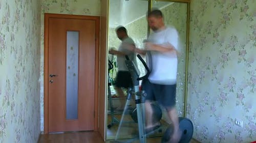Overweight Man Exercising On Trainer Ellipsoid -