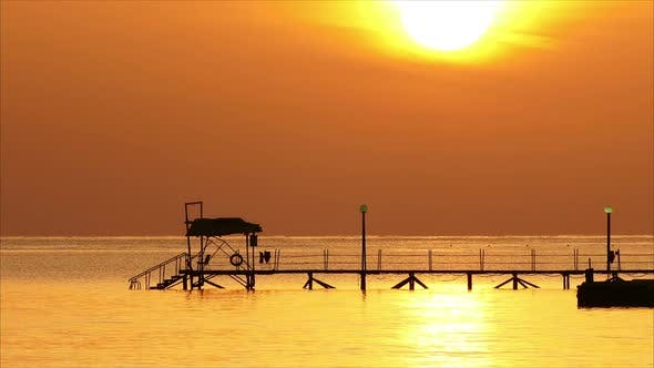 Thumbnail for Beautiful Sunrise Over Pier In Sea - Filmed At Telephoto Lens,
