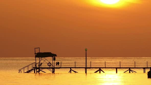 Thumbnail for Beautiful Sunrise Over Pier In Sea - Filmed At Telephoto Lens, Zoom Out