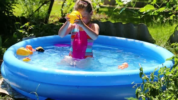 Thumbnail for Cheerful Girl In Inflatable Pool In Summer Garden 5