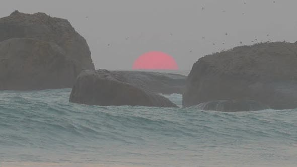 Thumbnail for Big Red Sun Is Setting In The Sea Between The Rocks