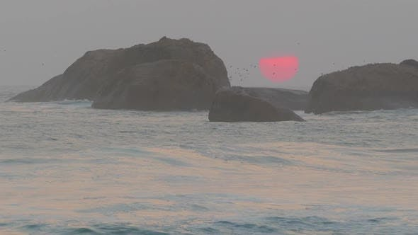 Cover Image for Big Red Sun Is Setting In The Sea Between The Rocks - 1
