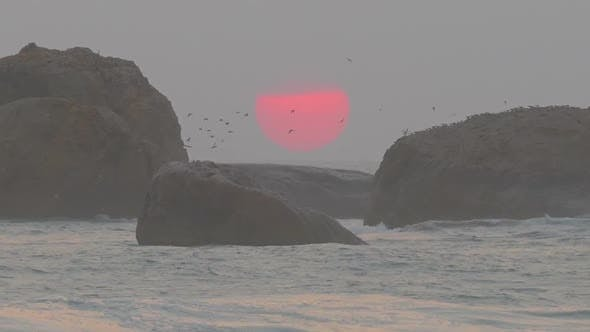 Thumbnail for Big Red Sun Is Setting In The Sea Between The Rocks - 2