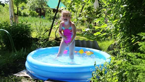 Thumbnail for Cheerful Girl In Inflatable Pool In Summer Garden 3