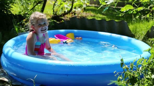 Thumbnail for Cheerful Girl In Inflatable Pool In Summer Garden 4