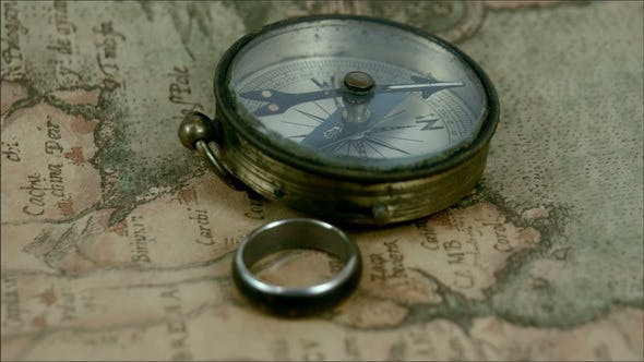 Thumbnail for A Compass and a Ring on Top of the Map