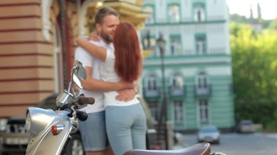 Couple Embracing By The Scooter