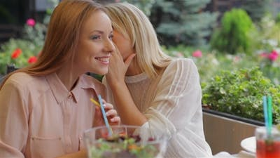 Girls Whispering In The Cafe