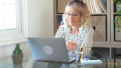 Adult woman type on laptop computer and smile happy for smart working free office home activity