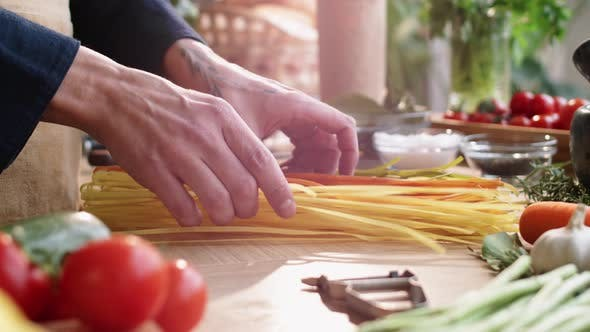 Thumbnail for Hands of Male Chef Preparing Multicolored Spaghetti for Cooking