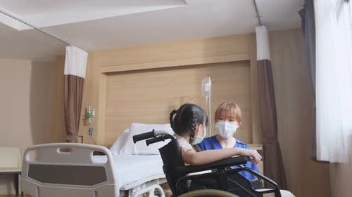 Asian nurse wear mask, taking care of kid patient sit on wheelchair in recovery room in hospital.