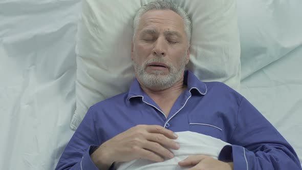 Thumbnail for Senior man loudly snoring and puffing in bed, sleeping problems at old age
