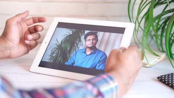 Businessman Holding Digital Tablet Discussing Ideas in Video Conference