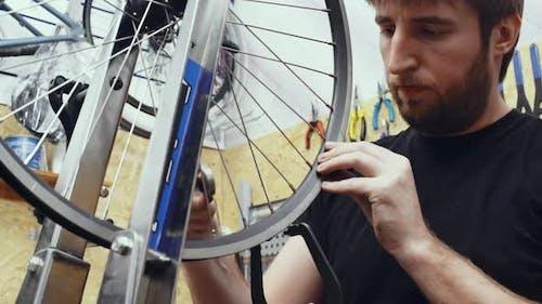 Mechanic Repairing Wheel in Workshop