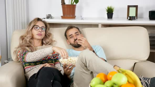 Thumbnail for Revealing Shot of Couple Eating Popcorn and Watching TV in Living Room