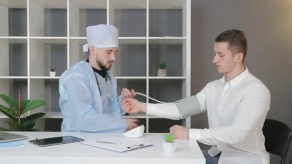 Thumbnail for Male Doctor in the Office Measures the Pressure of a Male Patient.