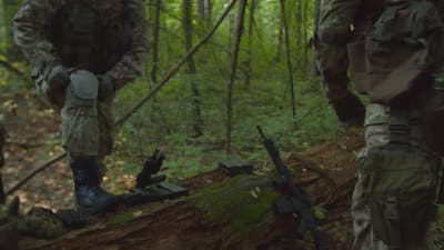 Military Squad Getting Ready for Reconnaissance Operation in Forest