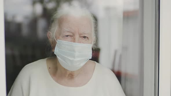 Portrait Of Old Woman In Medical Mask. Woman Looking Out The Window.