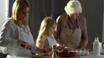 Little Girl Cooking with Mom and Grandma