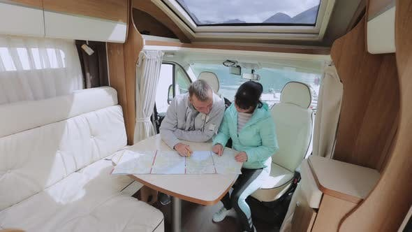 Thumbnail for Couples in RV Camper Looking at the Local Map for the Trip