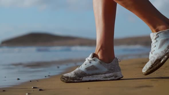 Cover Image for Close-up of the Girl's Feet in Sneakers Fit on the Sand To the Ocean. SLOW MOTION STEADICAM