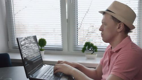 Man Freelancer in Hat Sitting at Table and Typing Text on Laptop Window Background