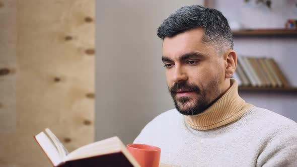 Cover Image for Bearded Man Reading Interesting Book and Drinking Tea or Coffee, Leisure Time