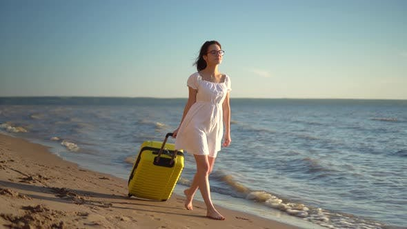 Thumbnail for Young Woman Walks Along the Beach of the Sea with a Yellow Suitcase. A Girl in a White Dress Walks