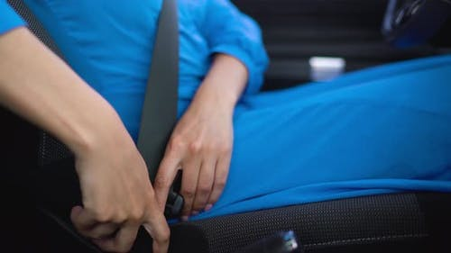 Woman Unfastening Car Safety Seat Belt While Sitting Inside of Vehicle After Driving