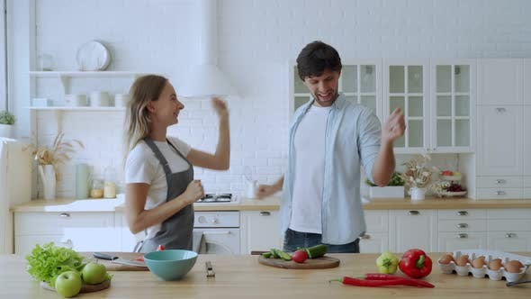 Thumbnail for Young Couple Dancing at Home Kitchen. Preparing Food at Home, Husband and Wife Having Fun Cooking