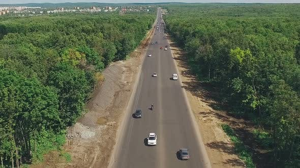 Thumbnail for Drone Is Flying Over Long Straight Highway Through Dense Forest, in Sunny Summer Day