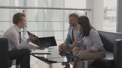 Sales Representative Showing Documentation to Couple in Dealership