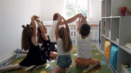 Positive Young Teacher Does Developing Exercises for Fingers in Light Living Room