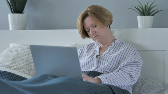 Thumbnail for Old Senior Woman Sleeping and Working on Laptop in Bed