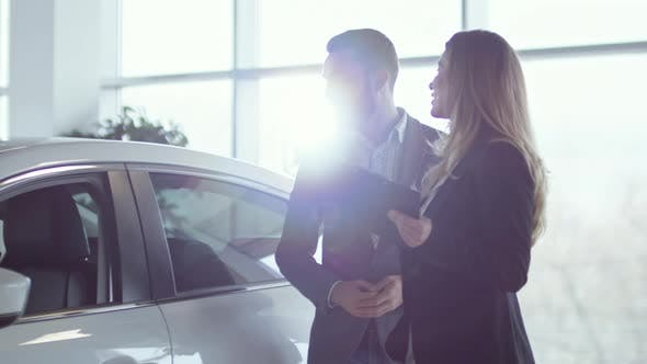 Thumbnail for Saleswoman Showing New Car to Rich Client