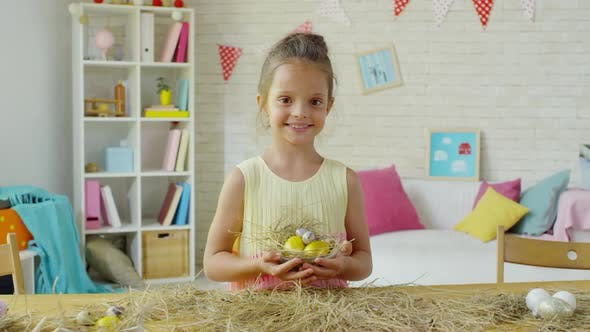 Thumbnail for Happy Little Girl Posing with Easter Eggs in Hay Nest