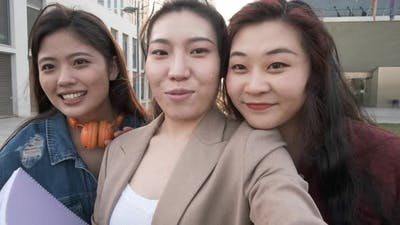 Three asian women taking a selfie. Student friends on the university campus.