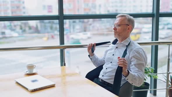 Thumbnail for Senior businessman wears white shirt and drinking coffee near big window with city view