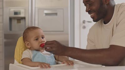 Father Feeding Toddler with Strawberry