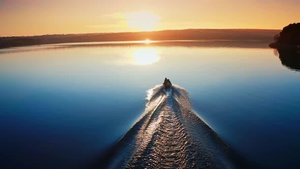 Thumbnail for Motorboot schwimmt auf dem Fluss bei Sonnenuntergang
