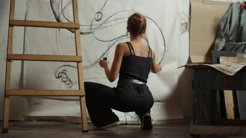 Artiste féminine accroupie en studio