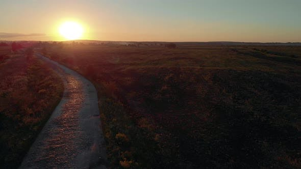Scenic Countryside Landscape with Rural Road at Sunset