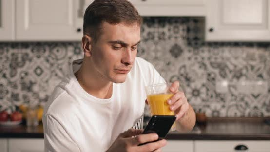Thumbnail for Man Drinking Juice While Using Smartphone
