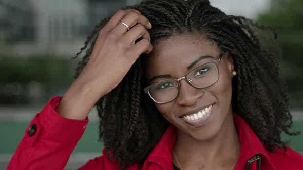 Thumbnail for Afro-american Woman Looking at Camera, Smiling, Correcting Hair