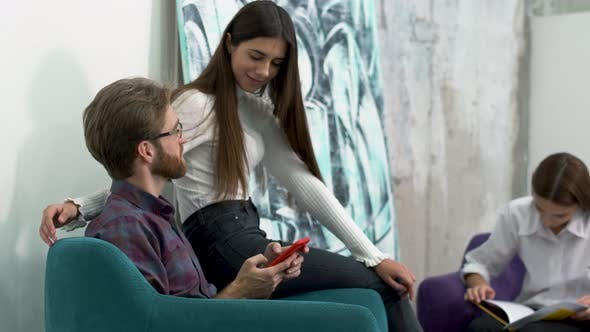 Cover Image for Employees Relax on a Chair in a Hub, and Pretty Girl Gently Runs Through the Guy's Hair