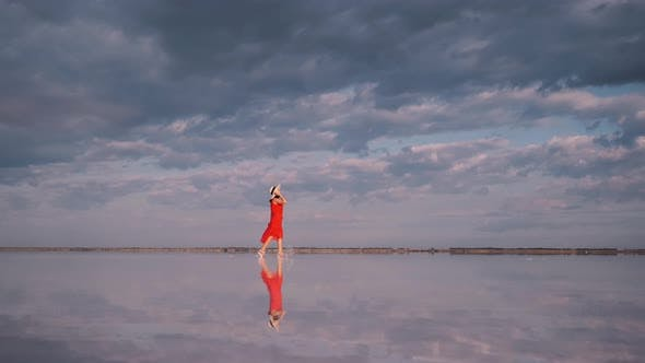 Thumbnail for Young Woman in a Waving Dress Walks Along a Pink Lake in Which Clouds Are Reflected