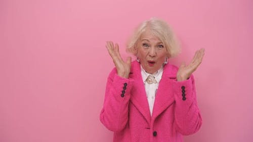 Cheerful Mature Woman in Stylish Pink Coat Gestures Happy Surprise on Isolated Background