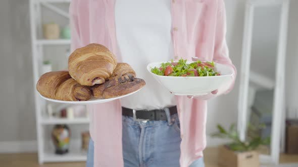 Young Caucasian Woman Holding Plates with Organic Salad and Crusty Croissants
