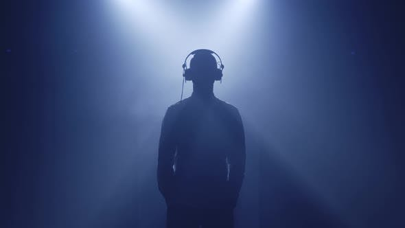 Backlit Silhouette of Dj Man Standing in Dark Nightclub Disco Putting Headphones on To Listen Music